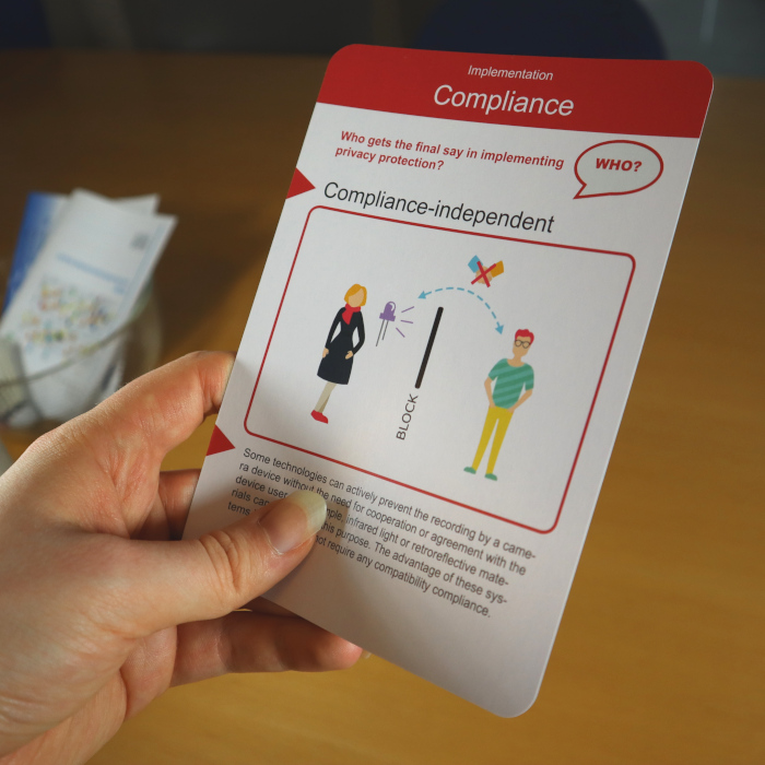 A hand is holding a card with a red heading in front of a wooden